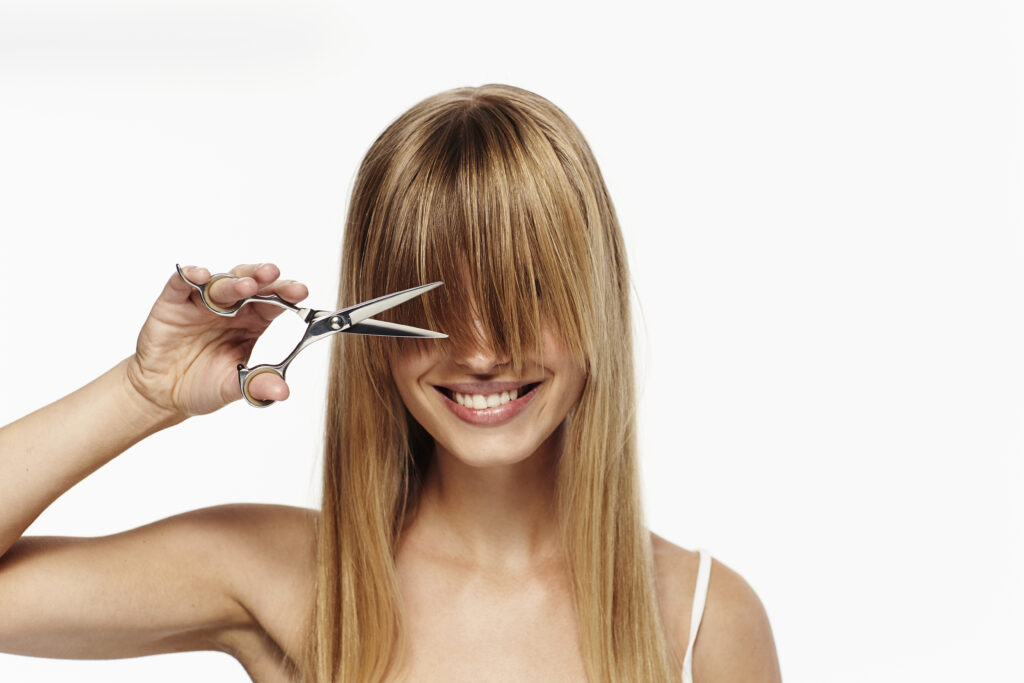 Une femme sur le point de couper sa frange avec un ciseaux. Elle sourit.