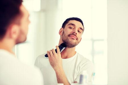 homme avec tondeuse barbe