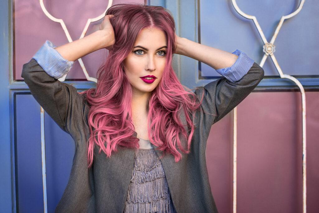 Femme aux femmes colorés rose flashy, elle porte une coloration temporaire.  Retrouvez les colorations temporaires sur beautycoiffure.com
